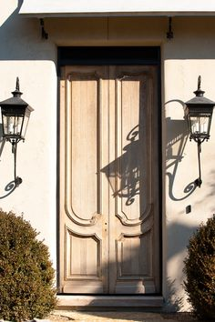Natural Wood French Country Double Front Door in a Stucco Wall with Gas Lanterns
