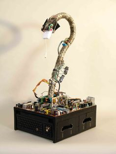 """Our reptilian friend has a """"mouse"""" lunch. He is rising from a rough terrain of computer power supplies. The terrain is flanked by two Mac keyboards and a series of 5-1/4"""" floppy diskettes."""