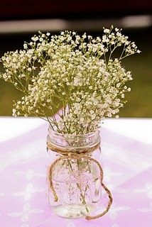 This can't be very expensive.  Cute centerpiece idea for tables - mason jar, raffia/twine, baby's breath