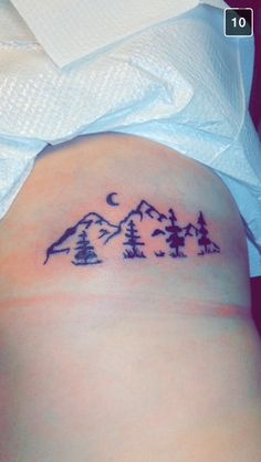 Mountain tattoo with trees and moon on ribs