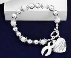These white ribbon bracelets have white and silver beads with 2 charms. A heart charm that is engraved with the words Where There is Love