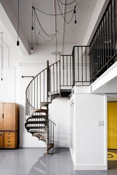 A cast-iron spiral staircase, re-purposed from a historic building in London's Portland Place, leads up to the mezzanine of this workspace within a 19th-century schoolhouse.