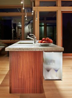 The island in this kitchen has a suspended glass cabinet with hidden LED lighting.