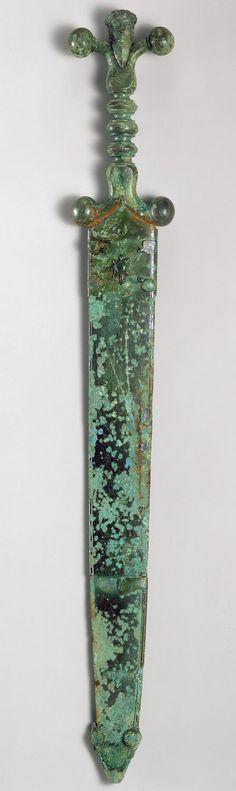 Sword and Scabbard  Date: ca. 60 B.C. Culture: Celtic Medium: Iron blade, copper alloy hilt and scabbard Dimensions: Overall: 19 5/8 x 2 5/8 x 7/8 in. (49.8 x 6.7 x 2.2 cm)