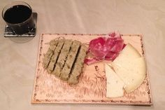 A Spanish snack of jamon and assorted cheeses, homemade unleavened bread with herbs, and a glass of Rioja wine.