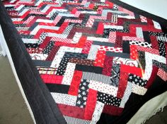 This dramatic red, white and black bed runner was made from 297 rectangles of different fabrics. Done in the prairie braid style, this quilt will be a dramatic addition to your bed. Made to lie on the end of the bed to cover your legs and feet to add extra warmth. Great on a cool night when you don't want a full size quilt. Made from high quality cotton fabrics and cotton batting. Backed with a fun red fabric and finished off with a black fabric for borders and binding. Machine quilted.