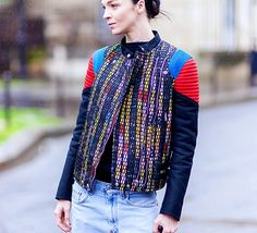 Multi-colored jacket, black sweater tucked in to light-washed jeans