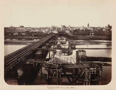 Budowa rusztowań przy nowowybudowanych filarach przyszłego Mostu Aleksandryjskiego. Po lewej stronie widoczny tymczasowy, drewniany most. Widok w kierunku Starego Miasta.