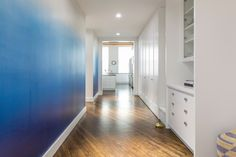 One half of a loft hallway in Williamsburg is demurely white; the other is ombre blue. Design by Glickman Schlesinger Architects. Photograph by Lauren Coleman.