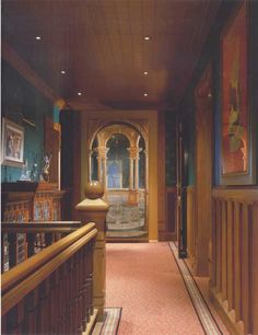 The upstairs hall features an 18th-century mirrored Venetian trompe l'oeil mural; the Herter Bros. cabinet has sparkling LaFarge glass doors. Wool carpet is by Saxony. (Photo: Robert Benson)
