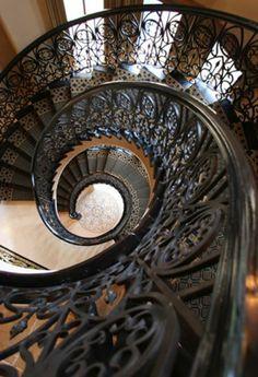 escalier quart tournant avec un rambarde en fer noir et bois foncé
