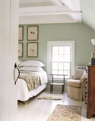 Soothing Bedroom  Soft green walls and a white-painted floor give this master bedroom a soothing appearance. A collection of framed 19th-century pressed leaves and flowers substitute for a traditional headboard. [Bed between regular-sized windows. Side with main door has chair in the corner and a dresser.]