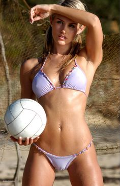 This image is clearly focusing on this woman's body. In minimal clothing, and having her skin glistening with sweat, this image sexualizes the sport of volleyball specifically for the viewer. Instead of viewing this woman as an athlete, one looks at her as an in-shape swimsuit model who happens to be holding a volleyball.