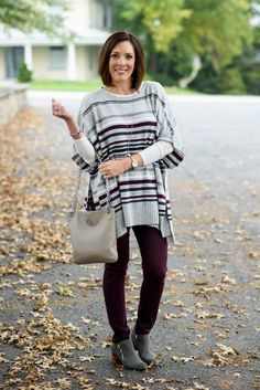 The perfect cozy fall casual look: striped poncho with aubergine skinnies and grey ankle boots!