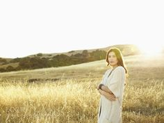 Beautiful woman in nature standing in a grassy field backlit by the sun wrapped in a sweater looking by gabledenims. Please Like http://fb.me/go4photos and Follow @go4fotos Thank You. :-)