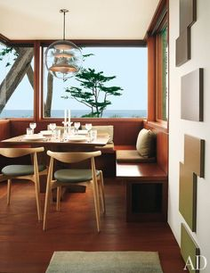 Dining room with a view. We love the built-in seating with Hans Wegner CH20 elbow chairs.