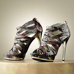 These Jennifer Lopez dress sandals feature a snakeskin pattern, metallic accents and a caged design.