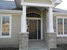 Stone or brick at the entrance with an eyebrow transom can give a home curb appeal. This custom home with pillars has the Craftsman charm.