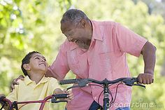 Grandfather and grandson on bikes outdoors smiling in the park