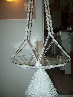 A white plant holder table hanging from the ceiling....my work!!!!