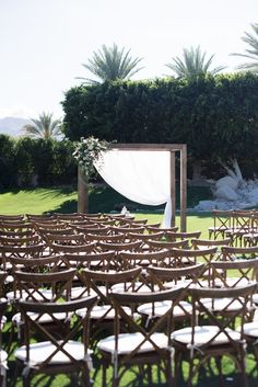 Arrangements Floral + Party Design — Rancho Mirage, Lauren + Chris | Wooden Canopy with wooden cross back chairs, outdoor desert wedding, white and green