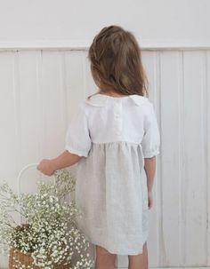 Lniana sukienka z kołnierzem. Góra w kolorze białym, spódnica w drobne, szare paski to skromne, ale efektowne połączenie. Len, którego użyliśmy jest antyalergiczny a skóra nie poci się w nim.