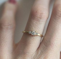 Simple and dainty three diamond ring. Other gemstones available are: ruby, emerald, sapphire, black diamond, pearl, amethyst... IF YOU WANT A CUSTOM ring please contact me before purchase. Product details: - 14k/18k solid gold band - diamond total carat weight 0.26 carat - middle