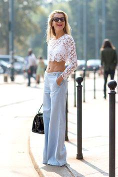 Milan Fashion Week spring 2014, Street style. Natalie Joos in cropped white lace blouse, light blue flared trousers.