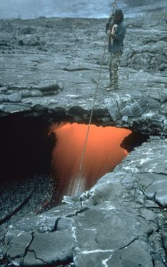 Scientist measuring height of lava flowing in a lava tube, Kilauea Volcano, Hawai`i. Photograph by K.V. Cashman in 1994