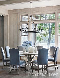 "A ""Lola"" chandelier from Bungalow Classic hangs above the round elm dining table. Floors throughout the first level are wide-plank oak. - Photo: Emily Jenkins Followill / Design: Beth Webb"