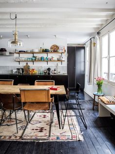 black stained floors and colorful rugs