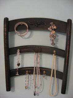 """a repurposed vintage chair has a new life  as a jewelry holder! fresh coat of jet black paint  distressed 3 rows of hooks and a vintage drawer pull hold all your jewels and looks cool too! hook on back for easy quick hanging! measures 14 3/8"""" wide x 16 3/4"""" tall jewelry not included"""