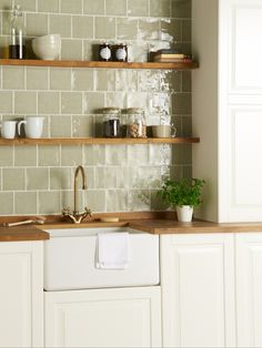 Green tiles are the perfect accessory to a country farmhouse kitchen. These 'Mere' tiles from The Winchester Tile Company are a subtle nod to the green tile trend and look gorgeous when paired with natural woods and foliage.