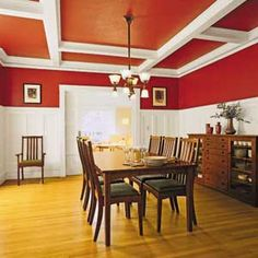 Dining room painted white below the chair rail and red above the rail and the ceiling.