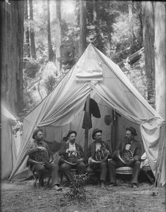 Four French hornists sitting in a tent in a clearing in the woods.  I'd like to know the story behind this.