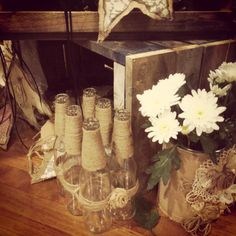 6 pack of glass bottles covered in twine and hessian rose buds