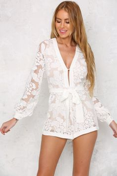 The Chardonnay Romper has stunning sheer lace detailing over an inner lining, long sleeves and a self-tying bow at the waist. The plunging V neckline has a button clasp and the invisible back zip makes for easy access. Wear with chunky wedges and a choker!  Romper. Lined. Cold hand wash only. Model is standard XS and is wearing XS. True to size. Print may vary in placement.  Non-stretchy fabric. Cotton/polyester.
