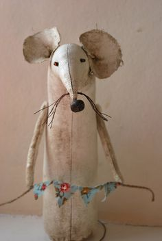 A very cute and quirky mouse. He is made from Calico and painted with acrylic. He has a little rusty tin bell nose and beady eyes. He is holding a little bunting banner with the words Love stamped on it. He measures 8x3.5 approx. He is antiqued with wax, and is free standing.  Please note he is not a toy but a little piece of mousy art. Please note also that these are made when ordered so will have slight differences.x