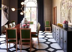 Interior designer Grant K. Gibson painted the floor of the dining room floor in the 2011 San Francisco Decorator Showcase in a black and white rug pattern. The green chair backs introduce a cool color which is balanced by the warm wood tones of the dining table. The purple-grey sideboard cabinet and the pale grey painitngs add layering with additional shades of grey. Image courtesy Traditional Home Magazine.