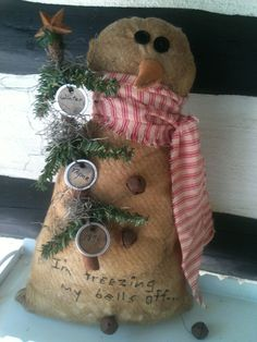 Snowman holding a twiggy tree trimmed in tags. Try saying that fast three times!