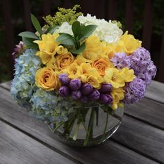 Teacher's Appreciation flower arrangement with yellow roses and freesia, purple hyacinths and tulips and hydrangeas, blue and white hydrangeas, and green fillers.