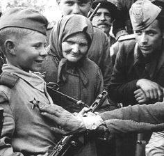"""A """"son of the regiment"""" wearing the Red Star for bravery, surrounded by his admirers. """"Sons of the regiment"""" were orphans adopted by Soviet regiments, and were looked after like the soldiers' own sons. They lived with the soldiers and fought alongside them in front-line actions. After the war, they found it difficult to adjust to civilian life, the company of other children and to children's activities."""
