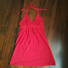 """VS bra top halter mini sundress Product Description: •Bright red bra top mini sundress from VS. Size medium. In great used condition. Feels like you are wearing your favorite tee shirt, but it's a super cute little sundress.   Fabric: •Shell:  •95% Cotton  •5% Spandex •Inner bra of the front panel:  •95% Cotton  •5 Spandex •Inner bra of the back panel:  •76% Nylon  •24% Spandex  Features: •VS bra top •Gold rings at the halter top •25"""" from armpit to bottom of the dress •14"""" arcross chest…"""