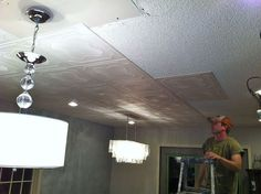 popcorn ceiling makeover low budget big impact, home decor, home maintenance repairs, painting, tiling, Installing the glue up ceiling tiles right on top of the popcorn ceiling