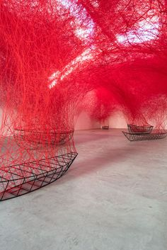 "Chiharu Shiota  ""Uncertain Journey"" installation 2016 : A Flotilla of Wireframe Boats Overflow With a Dense Canopy of Red Yarn"