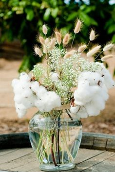 Consider adding a few non-floral elements to your centerpieces; these fluffy cotton sprigs look beautiful paired with small flowers, like ba...