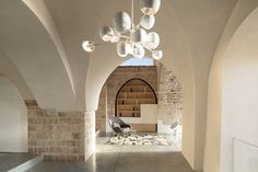 Aged stone walls punctuated by grand arched openings serve as a backdrop to the rooms within this Jaffa apartment, which has been overhauled by architecture practice Pitsou Kedem. Old Jaffa, Pitsou Kedem, Fabric Room Dividers, Aluminum Screen, Thing 1, Ancient Buildings, Apartment Interior, Windows And Doors, Old And New