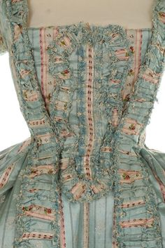 A fine striped brocaded silk robe à la Française, 1770s. of blue and white striped, figured and rose-sprigged satin, the open robe with 'sack-back', engageants, pleated and ruffled robings edged in silk fly braid, the matching petticoat with ruched furbelows and a stomacher made from the same fabric, bust approx 86cm, 34in
