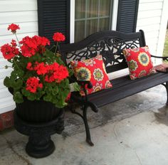 Our front porch May 2013 - I gave both the planter and the bench a fresh coat of black paint, then sewed up these colorful pillows for a pop next to the pretty geraniums.
