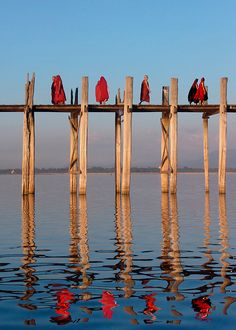 Buddhist Monks on U Bein's Bridge – Mandalay, Burma. The bridge is constructed entirely of teak and is reputed to be the longest wooden bridge in the world. It is located just outside the large city of Mandalay in Central Burma. A Buddhist Monstery is situated at the foot of the bridge.